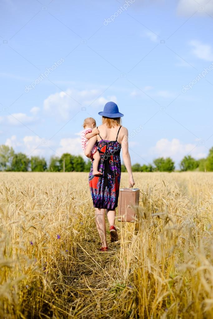 Young mother travelling with her child on hand on the wheat field