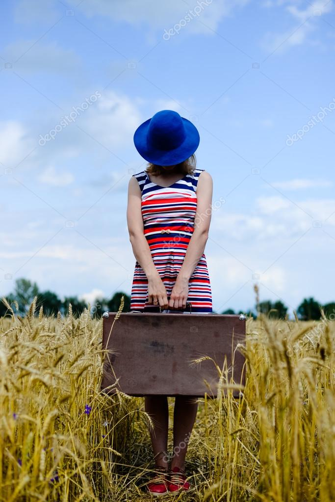 Elegant female wearing hat with valize walking away through wheat field.