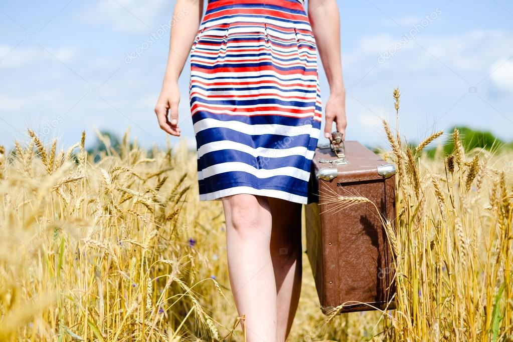 Picture of lower half of woman wearing dress with suitcase in field