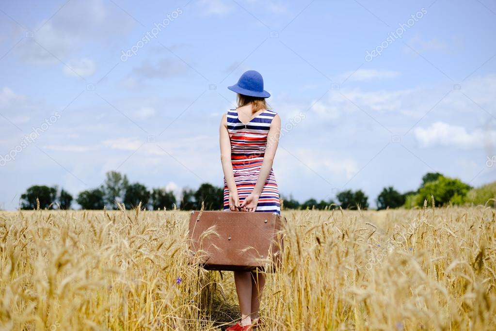 Romantic woman wearing hat with suitcase walking away through wheat field