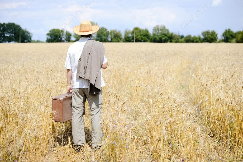 Picture of man with suitcase in the wheat field on sunny outdoors background