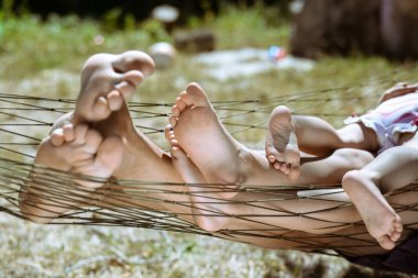 Closeup of happy family lying on hammock barefoot in summer