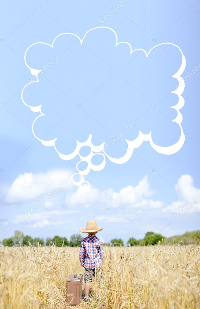 Little boy beside valize with thought bubble in summer countryside