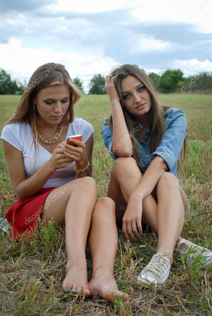 Two beautiful young ladies sitting together on summer