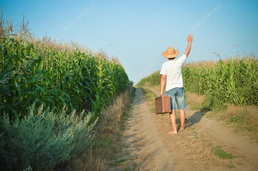 Back view of travel man holding suitcase on country road