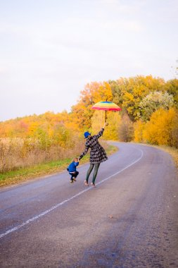 Happy mother and son having fun on autumn countryside road