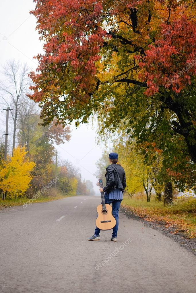 Beautiful young lady in jeans with guitar on countryside road