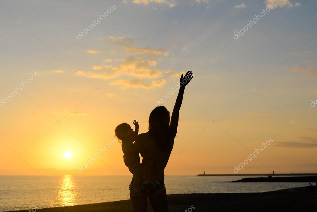 Silhouette of young exciting woman with hand up holding baby on dramatic seascape background