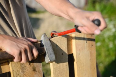 Closeup of hands with crowbar and hammer repairing wooden fence