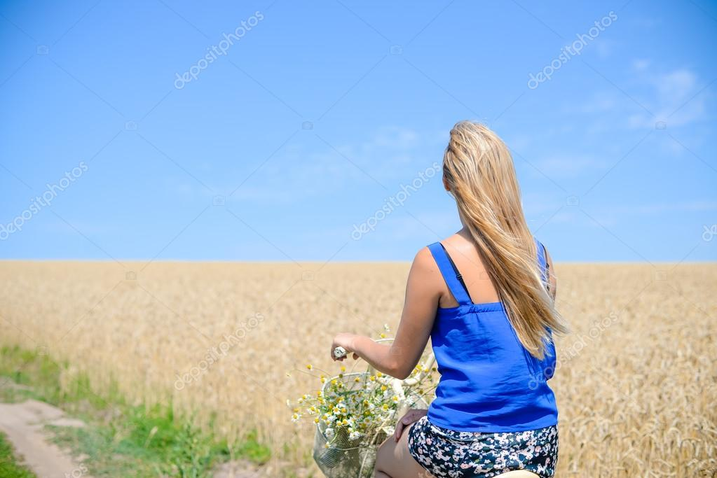 Backview of beautiful young lady riding bicycle through wheat field