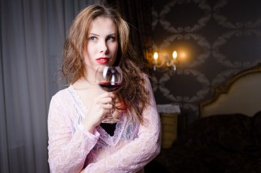 Picture close up of beautiful young woman on luxury bedroom background with a glass of wine