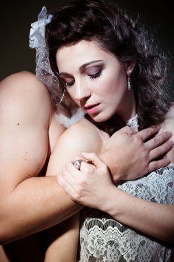 Picture of beautiful romantic couple on light background with eyes closed in hug