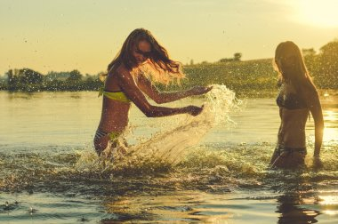 Picture of two beautiful girls best friends having fun and splashing water at sunset on sunny copy space background outdoors