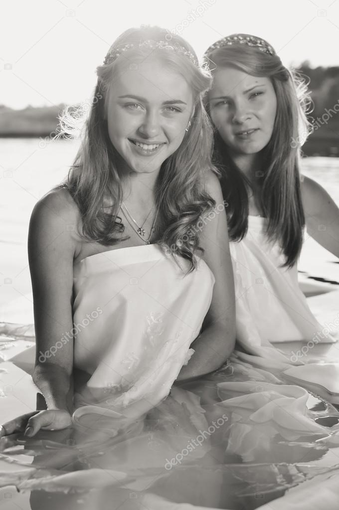 2 beautiful princess young ladies in white dresses on summer water outdoors background, black and white picture
