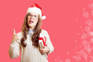 Picture of showing thumb up and holding present box beautiful young lady in Christmas hat, glasses happy smiling and looking at camera