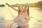 Picture of 2 beautiful princess young exciting ladies in white dresses on summer sunset water outdoors background