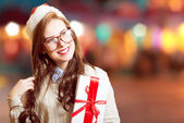 Picture of beautiful young lady in Santa red hat and glasses holding gift box
