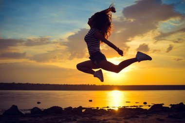 Image of beautiful young lady having fun jumping high over open water on summer outdoors copy space background