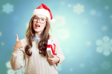 Showing thumb up and holding present box beautiful young lady in Christmas hat, glasses happy smiling and looking at camera