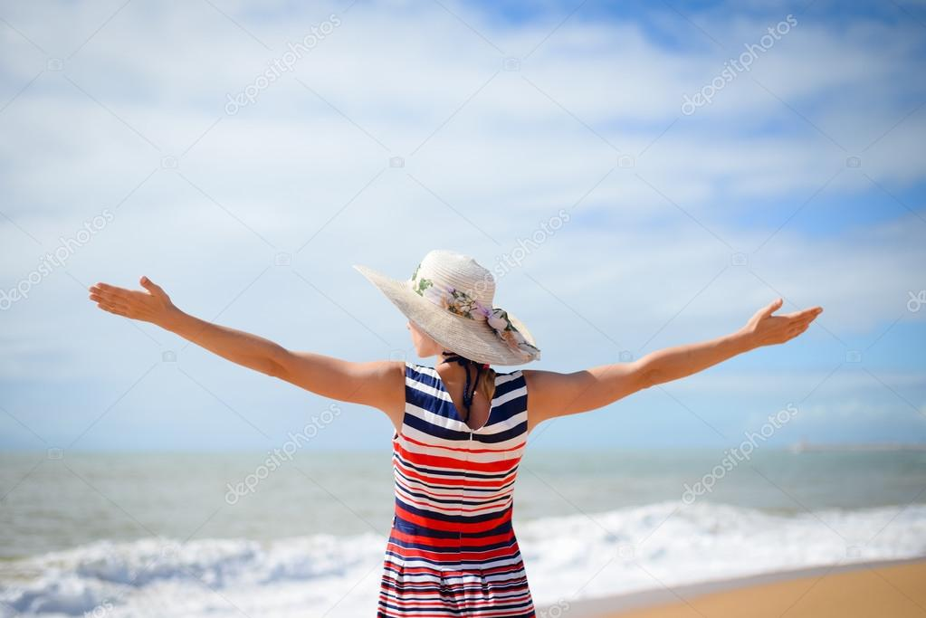Excited lady in hat spreading hands with joy facing sun