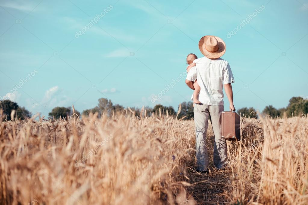 Backview of father holding baby and old suitcase in countryside