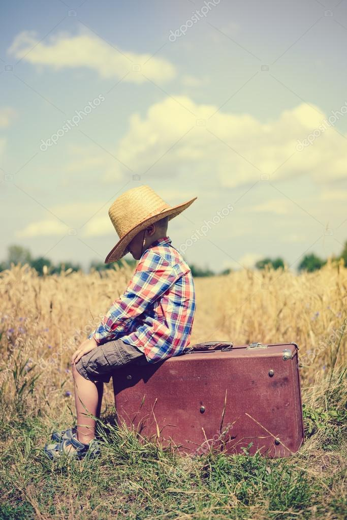 Sideview of little boy sitting on old suitcase in field
