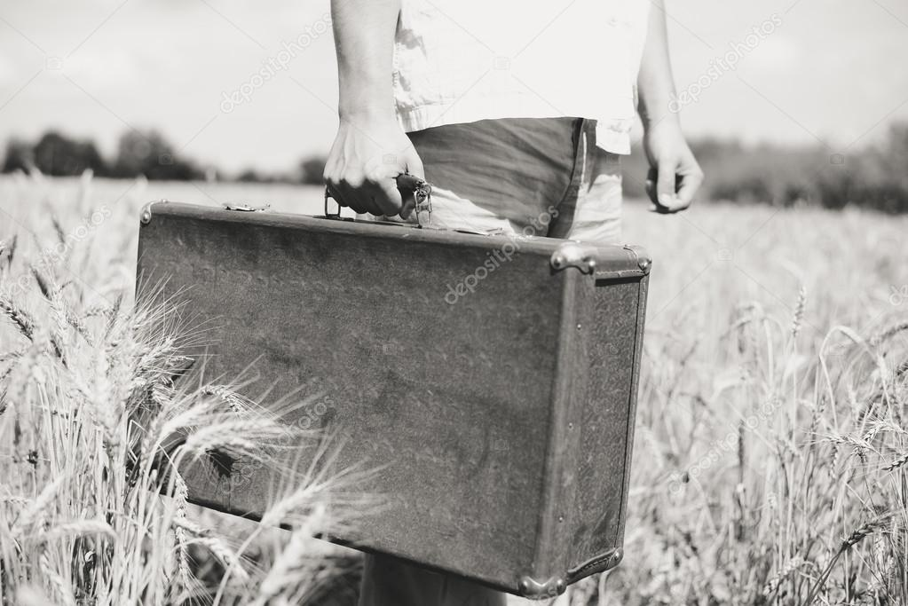 Black and white countryside image of hand holding retro suitcase