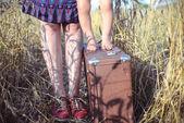 Fotografie Nahaufnahme der Frau und Baby auf Koffer in der Landschaft stehen