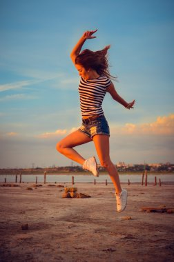 Image of beautiful active young lady having fun jumping high over open water on summer outdoors background copy space