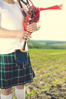 Closeup view of man enjoying playing pipes in traditional style. Green outdoors summer field background