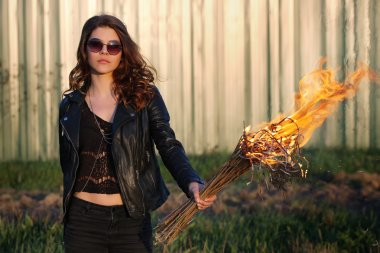 Young girl with glasses and a bully black jacket holding the torch outdoors