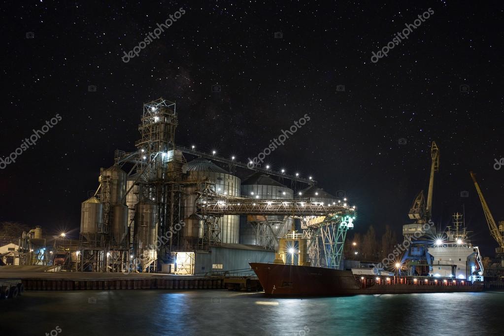 Fracht kran schiffs und korn trockner im hafen. bei nacht