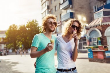 young couple walking and licking ice cream
