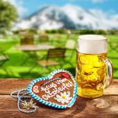 Oktoberfest-Konzept mit Ingwerherz mit dekorativem Zuckerguss und einem Glas Bier oder Pils im Freien auf einem urigen Wirtshaustisch in Bayern mit verschneiten Bergen