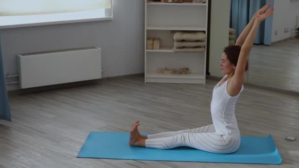 Mladá žena cvičí jógu ve studiu