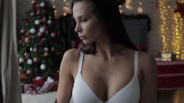Nádherná mladá modelka nosí různé stylové spodní prádlo během vánočních svátků doma
