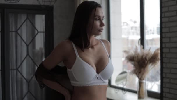 Gyönyörű fiatal női modell visel különböző elegáns fehérnemű karácsonyi ünnepek alatt otthon