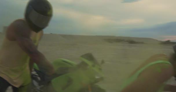 Krásný mladý pár muž a žena jsou na motorce spolu na pláži během západu slunce