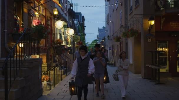 Lidé kráčející po Rue Du Petit Champlain, za soumraku