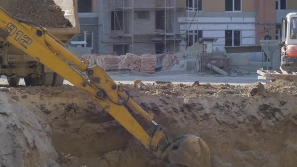 Excavator digging near a building under construction