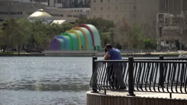 Pár se opírá o zábradlí u jezera