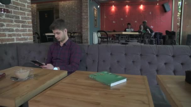 A man sitting at a table with a tablet