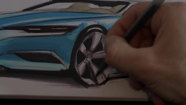 Close up of a hand drawing a car wheel