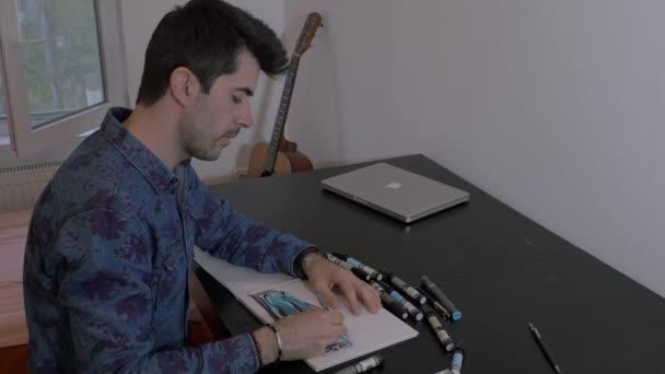 Muž sedí a kreslí