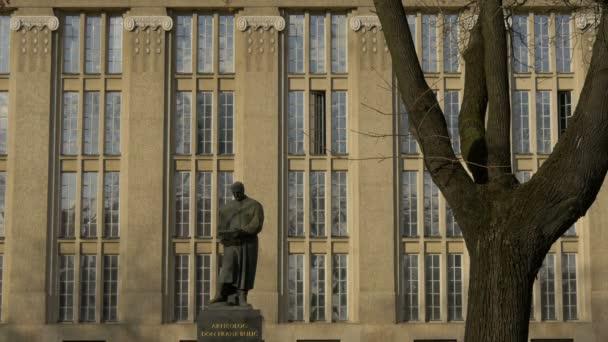 Socha muže u budovy s velkými okny