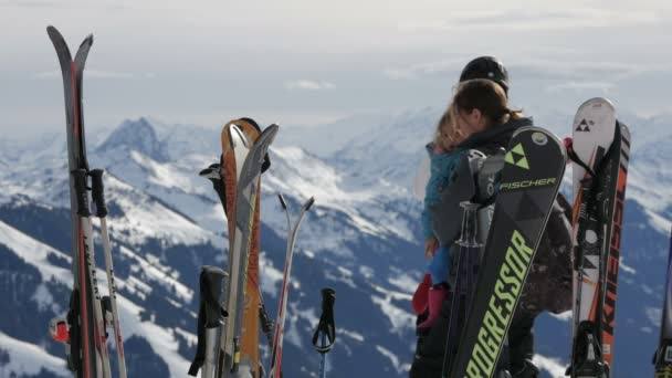 Skis stuck in snow with person and mountains on background