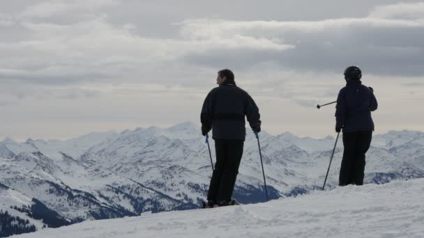 Skiers admiring landscape with snowy mountains