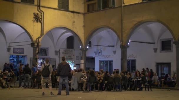 People relaxing at an outdoor restaurant in Pisa