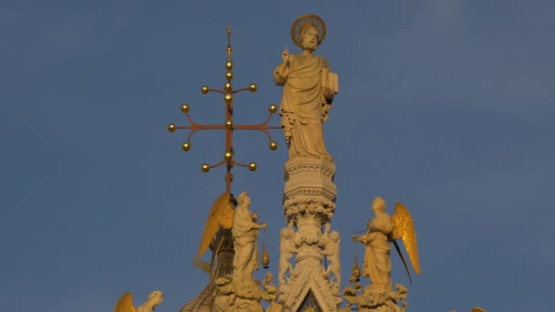 Saint with halo and angels statues