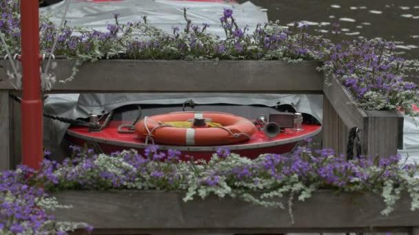 Lila Blumen in der Nähe eines festgemachten Bootes